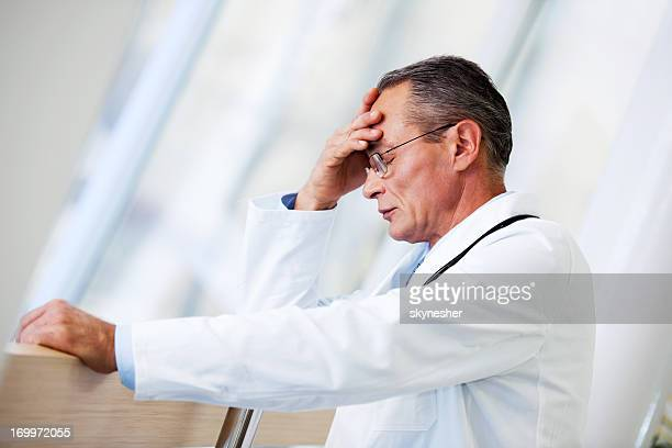 Mature adult doctor having a headache.