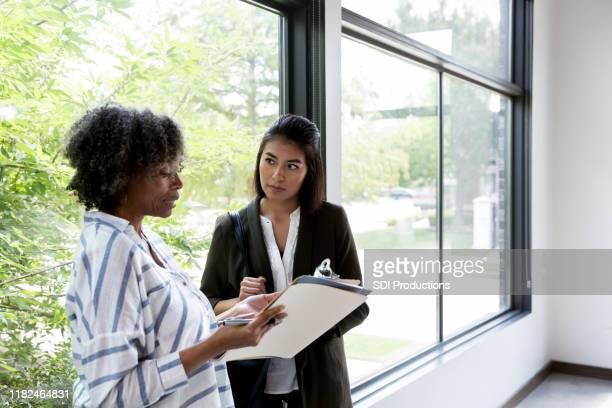 mature adult employee presents paperwork to business owner - businesswear stock pictures, royalty-free photos & images