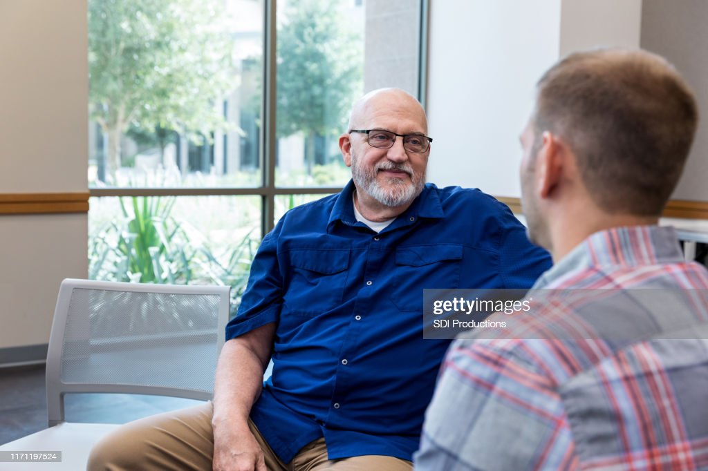 Mature adult father listens attentively to unrecognizable mid adult son : Stock Photo