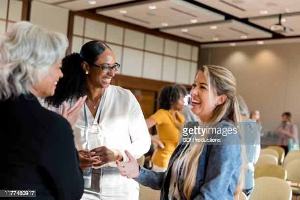 mature adult female conference speaker laughs with mid adult women - town hall meeting stock photos and pictures