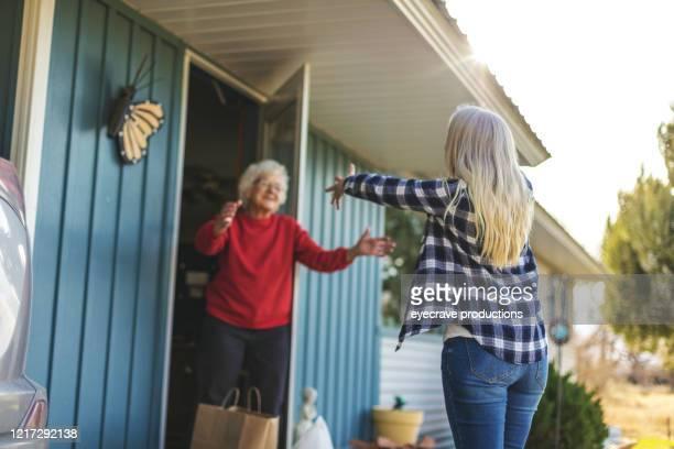 volwassen volwassen vrouw leveren boodschappen aan senior volwassen vrouwelijke en sociale distantiëring als gevolg van infectieuze virus uitbraak pandemie - actrice stockfoto's en -beelden