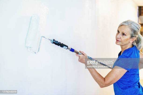 mature adult female painting walls white with paint roller - eyecrave  stock pictures, royalty-free photos & images