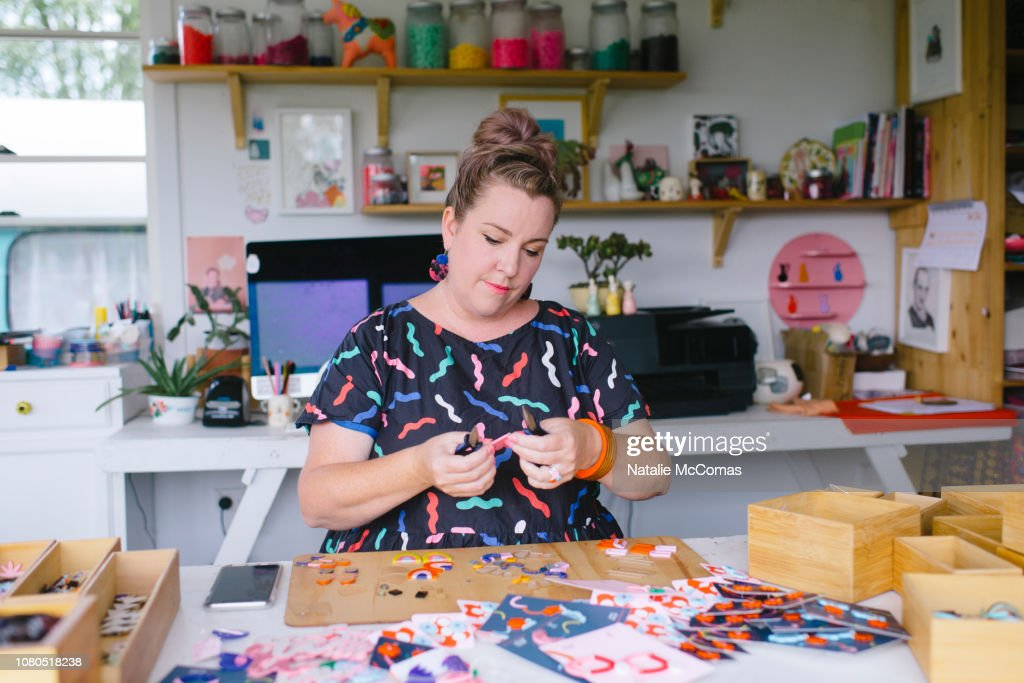 Mature adult female small business owner and designer working in studio office