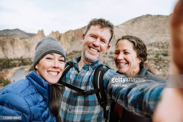 mature adult group hiking together in rugged area - smith rock state park stock pictures, royalty-free photos & images