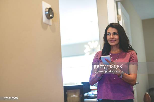 mature adult hispanic female operating smart climate control devices in her home through the use of smart phone in western colorado - energy efficient stock pictures, royalty-free photos & images
