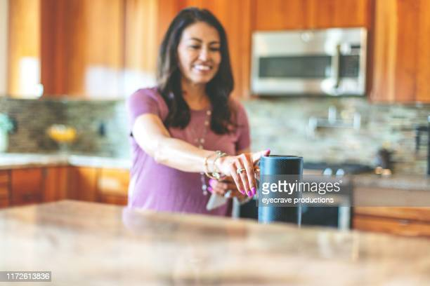 mature adult hispanic female operating smart speaker devices in her home through the use of smart phone in western colorado - bluetooth stock pictures, royalty-free photos & images