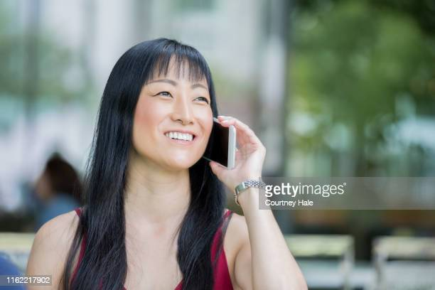 mature adult japanese woman smiles while making a call using a smart phone - telephone number stock pictures, royalty-free photos & images