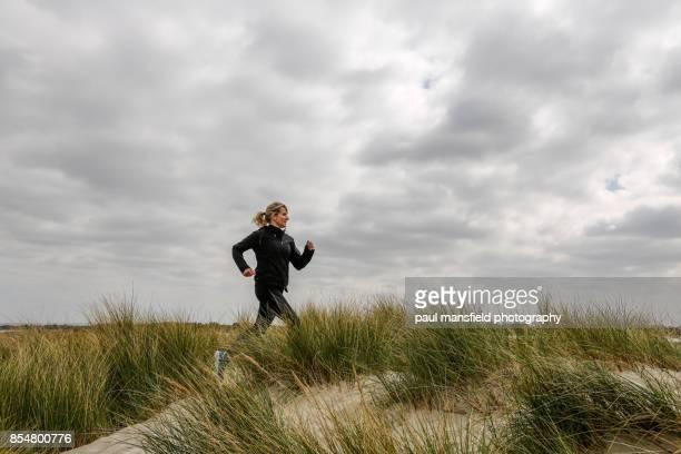 Mature adult lady running across grass sand dunes