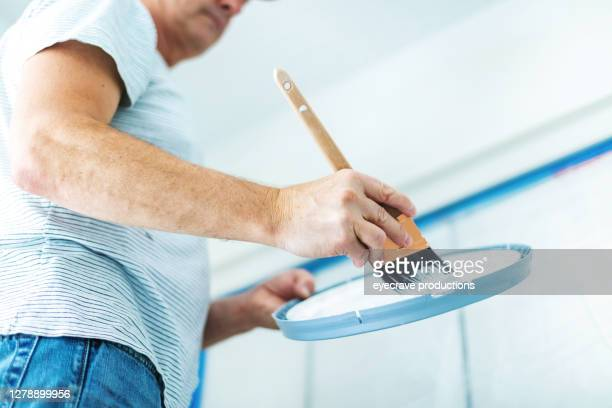 mature adult male dipping paintbrush into white wall paint - eyecrave  stock pictures, royalty-free photos & images