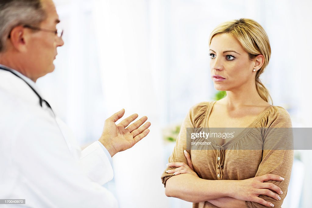 Mature adult male doctor talking to his patient. : Stock Photo