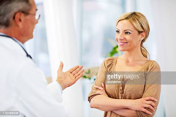 Mature adult male doctor talking to his patient.