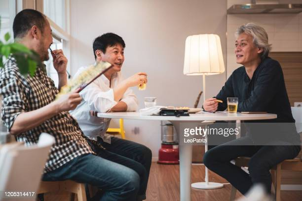 mature adult male friends at home during a dinner party - south korea stock pictures, royalty-free photos & images