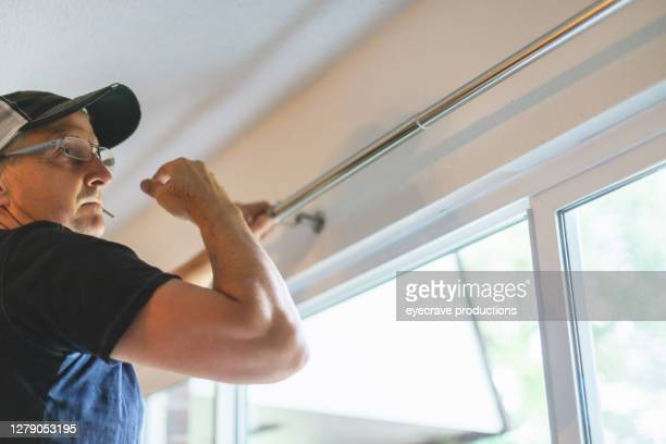 mature adult male installing curtain rods - eyecrave  stock pictures, royalty-free photos & images