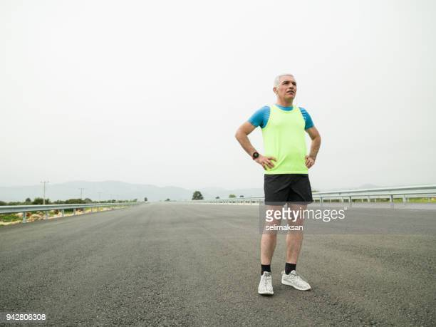 Mature Adult Man Getting Ready For Running On Asphalt Road