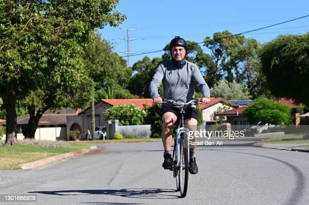 mature adult man riding on a bicycle - rafael ben ari - fotografias e filmes do acervo