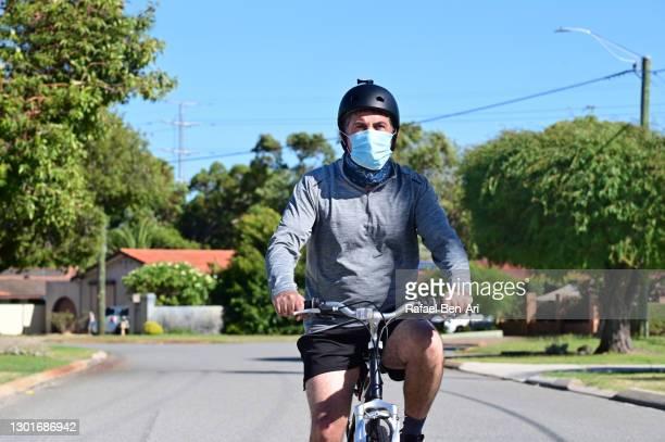 mature adult man riding on a bicycle wearing a face mask - rafael ben ari - fotografias e filmes do acervo
