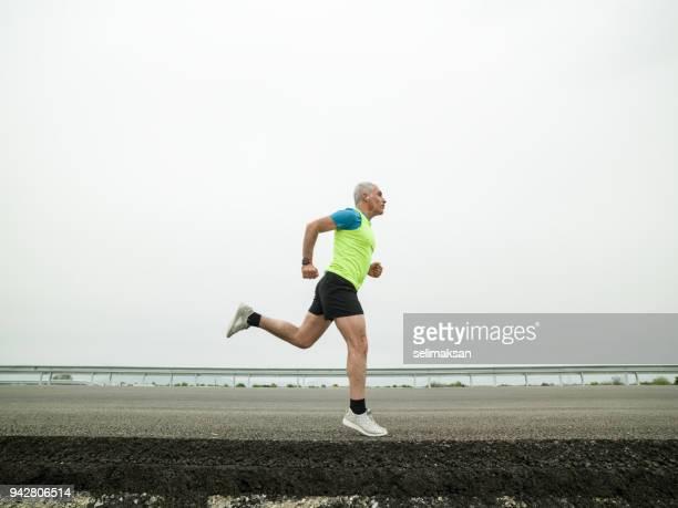 Mature Adult Man Running On Asphalt Road
