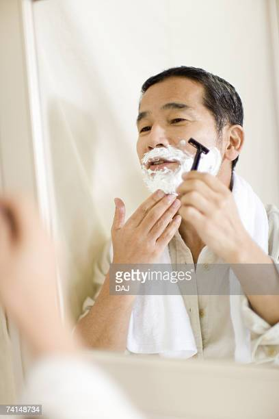 A Mature Adult Man Shaving Reflected in a Mirror, Front View, Side View, Differential Focus
