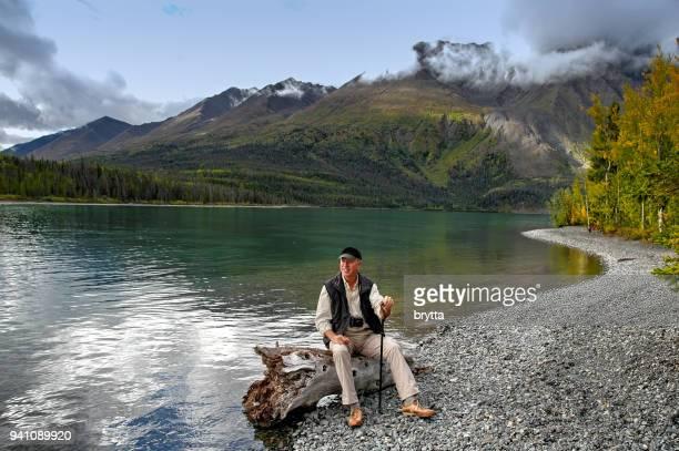 Mature adult man  sitting on a tree stump  near Kathleen Lake,Yukon,Canada