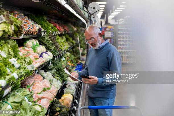 mature adult man texts wife about produce item on list - produce aisle stock pictures, royalty-free photos & images