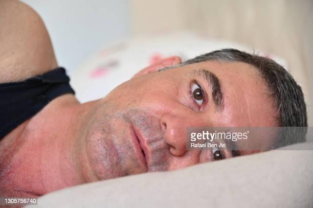 mature adult man waking up - rafael ben ari imagens e fotografias de stock
