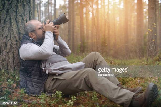 mature adult man walking in the woods and take pictures - digital camera stock pictures, royalty-free photos & images