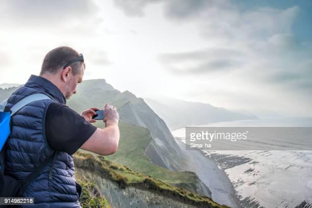 Hombre adulto maduro con un smartphone las fotografías el flysch de Zumaia. País Vasco. España.