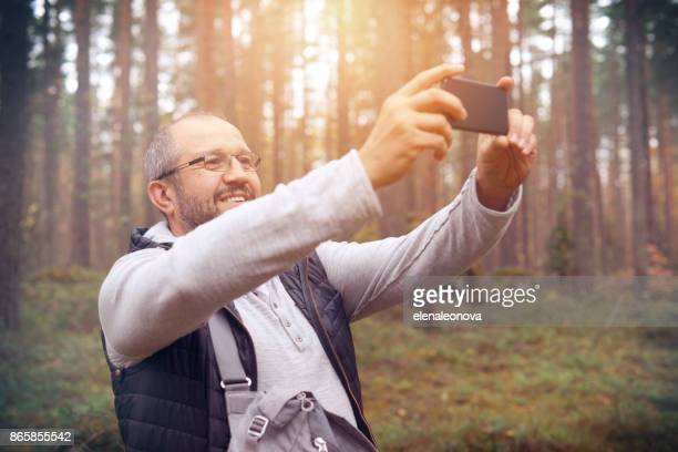 Mature Adult man with a smartphone ( selfie)