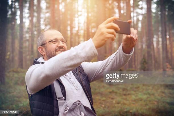 Hombre adulto maduro con un smartphone (selfie)