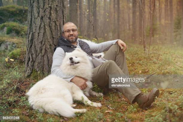 Mature Adult man with a white dog outdoors