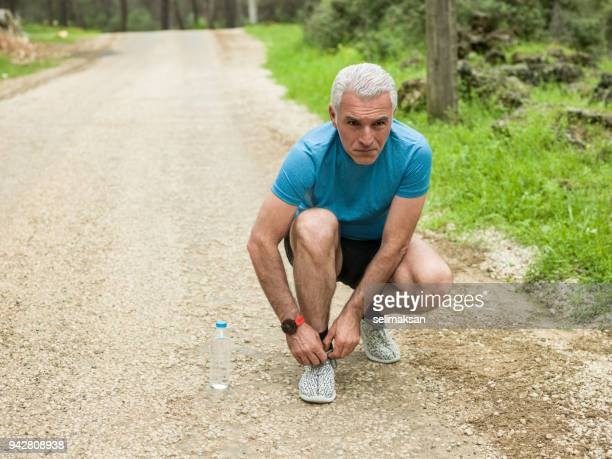 Mature Adult Man With Gray Hair Tying Shoelaces For Running