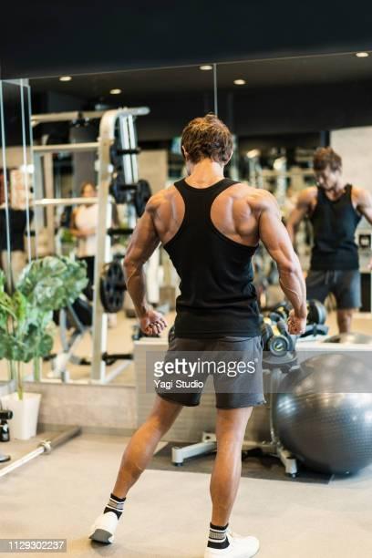 mature adult man working out at personal training gym - ランニングショートパンツ ストックフォトと画像