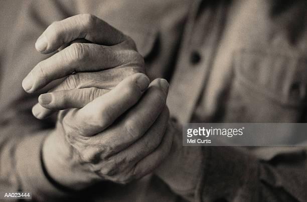 Mature adult rubbing hands, close-up (grainy B&W)