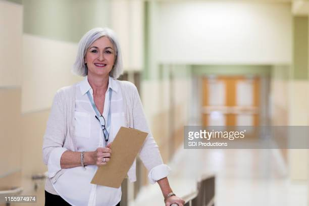 mature adult school counselor takes break in corridor - administrator stock pictures, royalty-free photos & images