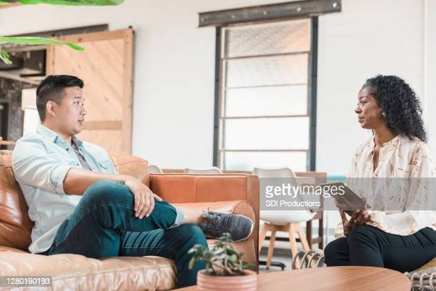 mature adult therapist listens to mid adult male client - psychotherapy stock pictures, royalty-free photos & images