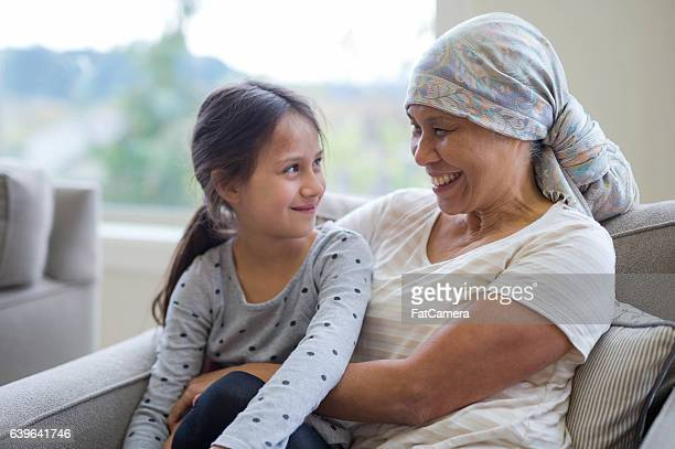 Mature adult with cancer smiling at her grandchild