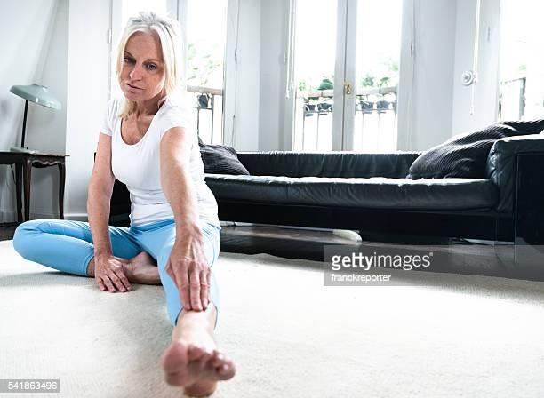 Ältere Erwachsene Frau yoga machen wie zu Hause fühlen.