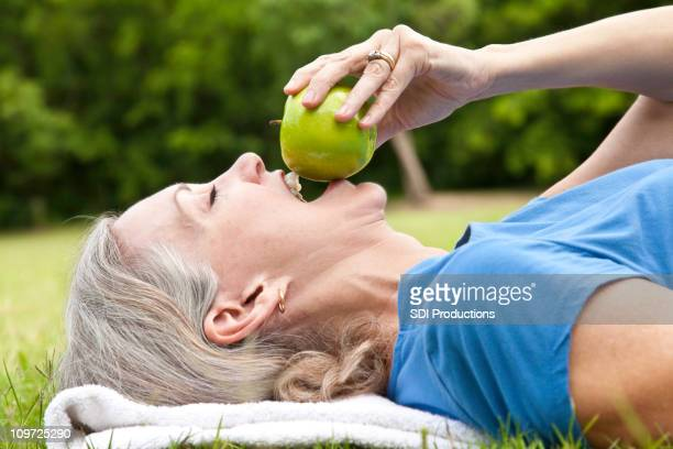 Mature Adult Woman Eating Apple Lying in the Grass