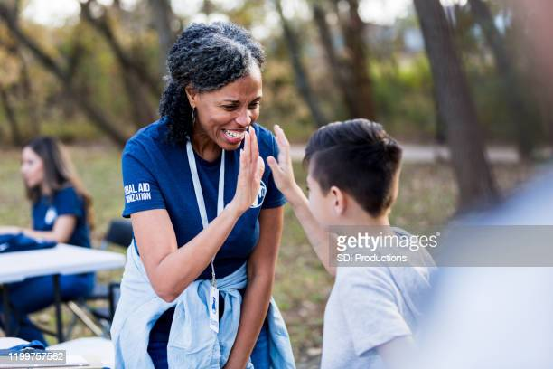 mature adult woman gives boy high five for volunteering - non profit organization stock pictures, royalty-free photos & images