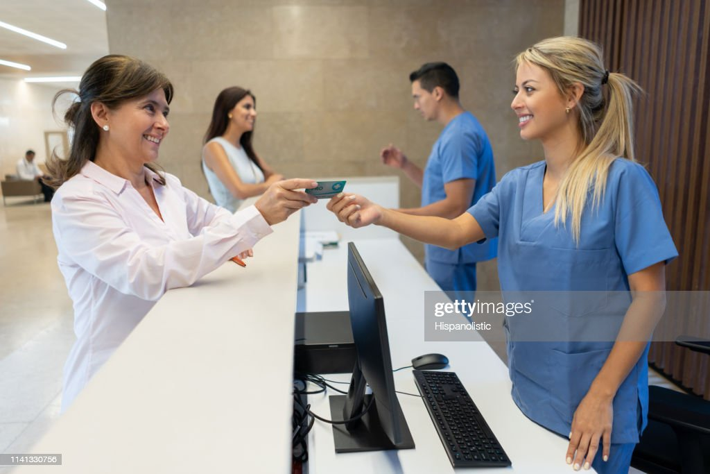 Mature adult woman handing her insurance card to nurse at the reception of the hospital both smiling : Stock Photo