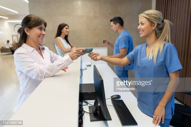 mature adult woman handing her insurance card to nurse at the reception of the hospital both smiling - medical receptionist uniforms stock pictures, royalty-free photos & images