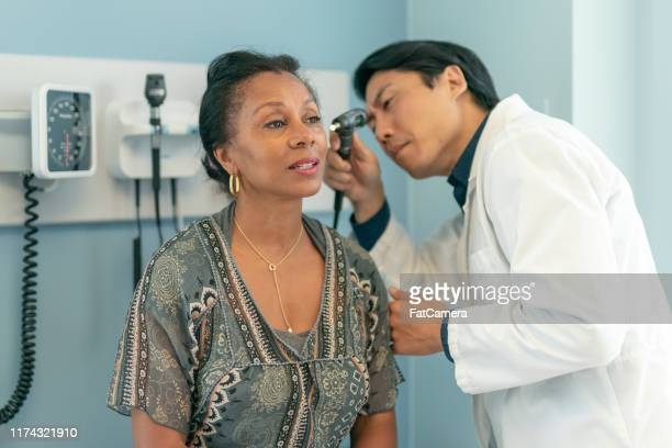 mature adult woman has ears checked by doctor at routine medical appointment - assistive technology stock pictures, royalty-free photos & images