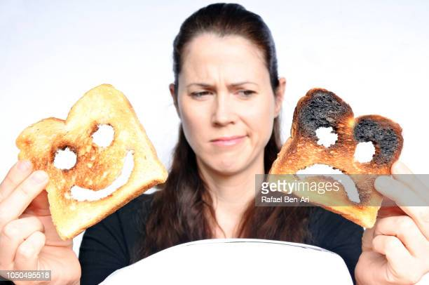 mature adult woman holding and looking at two different slices of toast bread - rafael ben ari fotografías e imágenes de stock