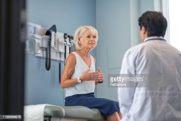 mature adult woman in medical consultation with male doctor - doctor's office stock pictures, royalty-free photos & images