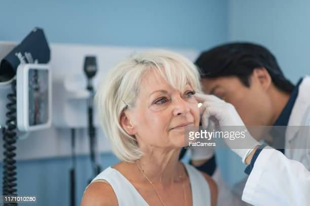 mature adult woman in medical consultation with male doctor - hearing aid stock pictures, royalty-free photos & images