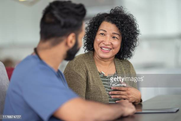 mature adult woman meeting with male doctor - patient stock pictures, royalty-free photos & images