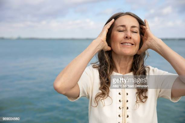 mature adult woman near the ocean - menopause stock photos and pictures