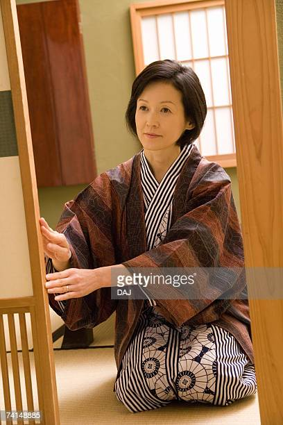 mature adult woman sitting and opening the sliding door, front view, three quarter length - three quarter length ストックフォトと画像