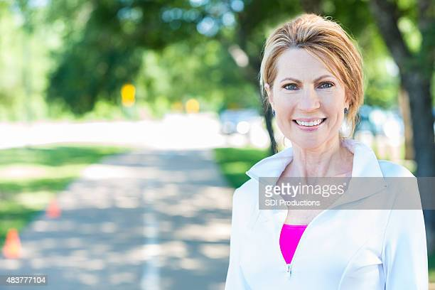 mature adult woman smiling after running on track in park - women's issues stock photos and pictures