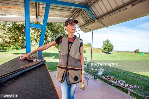 mature adult woman taking a break during target shooting training - stock photo - trap shooting stock pictures, royalty-free photos & images
